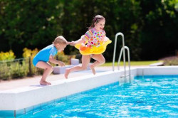 60370317-happy-little-girl-and-boy-holding-hands-jumping-into-outdoor-swimming-pool-in-a-tropical-resort-duri